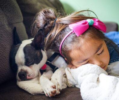 girl sleeping beside a dog on the sofa