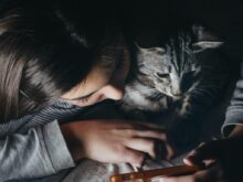 girl holding smartphone beside cat watching reclining to her shoulder